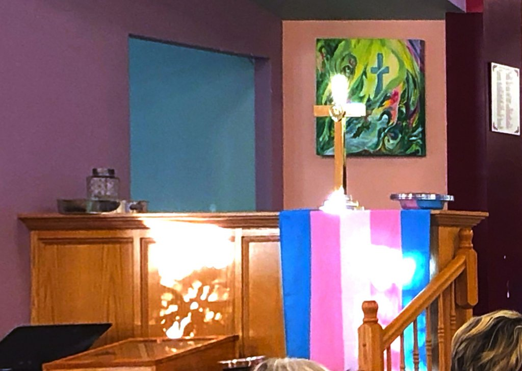A sunbeam finds the Trans Pride flag hanging on the left-hand altar
